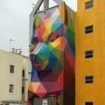 Colorful, Geometric Bear Mural Appears To Pop Out Of The Building