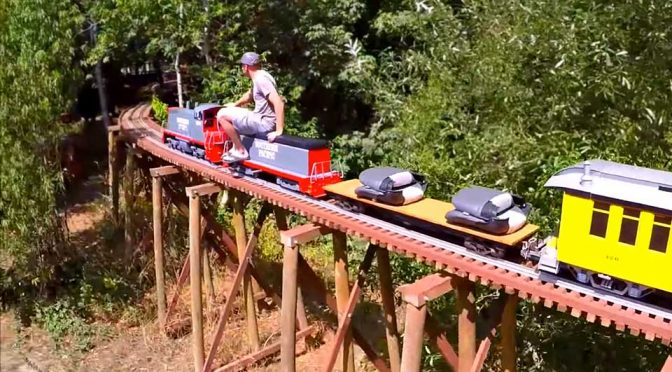 scale train moving on backyard railway trestle is simply